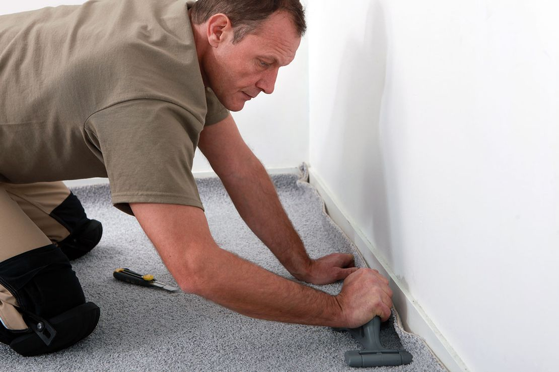 A professional carpet fitter, fitting a carpet